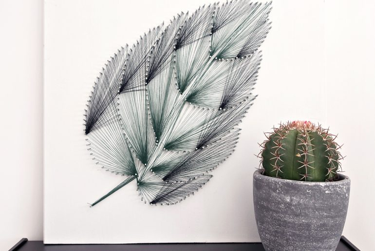 Leaf art made out of thread and nails